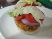 Arranging burger patty,onion tomato slice and lettuce over burger bun for veg burger recipe