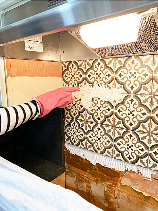 grouting the tiles on the backsplash with gloves