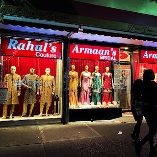 A shop window on 74th Street in Jackson Heights features South Asian fashion.