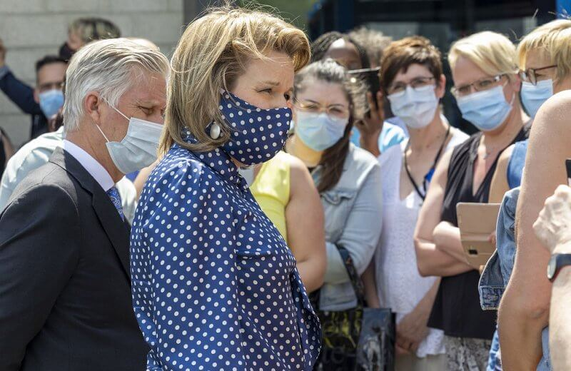 Queen Mathilde wore a navy polka-dot print tie neck blouse from Natan, and polka dot mask, white trousers