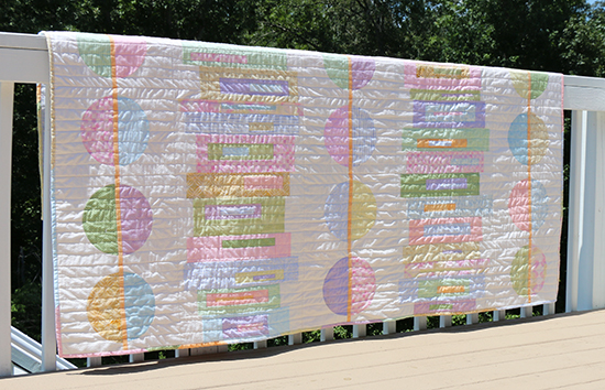 Front of Pastel Modern Quilt Featuring Circles and Stacked Rectangles