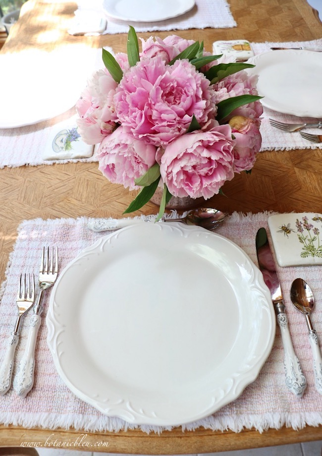 French country early summer table setting with white dishes and pink peonies