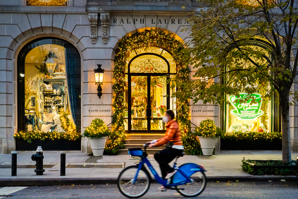 a photo of a lady riding a bicycle past christmas decorations in new york city