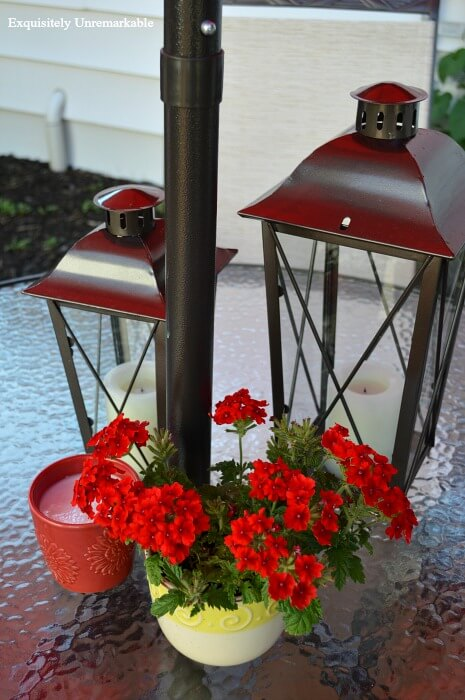 Metal Lanterns on a patio table with candles and red million belles in a yellow and white planter
