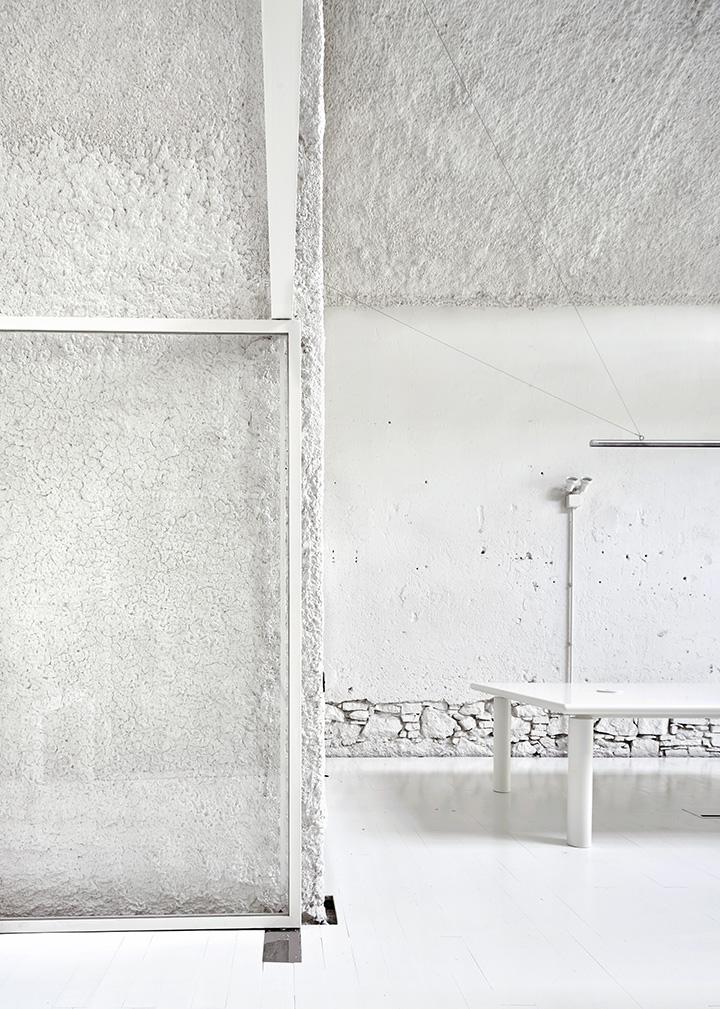 Los cerramientos de vidrio, el suelo de madera, las vigas remachadas y las paredes de mampostería todo en blanco