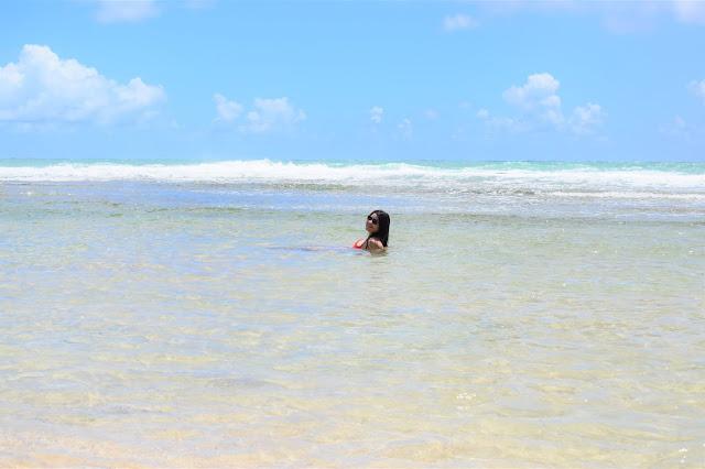 mulher morena boiando no mar