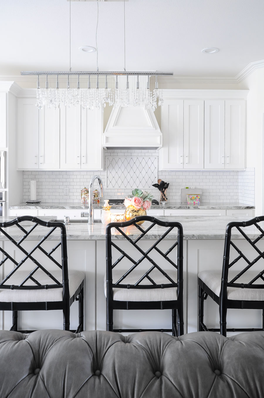 Bright white kitchen with fantasy brown granite, marble backsplash, thassos mirrored backsplash and lucite cabinet and drawer pulls. The Dayna counter stools from Ballard Design are gorgeous!