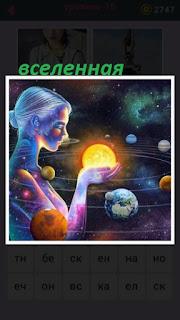 женщина создавая иллюзию держит в руках планеты во вселенной