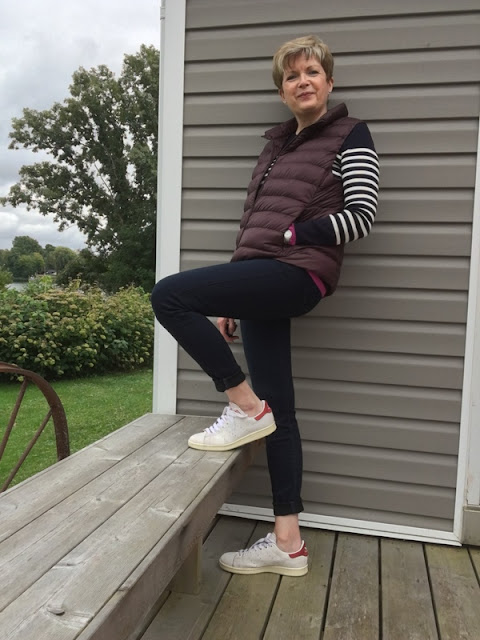 woman in striped sweater, jeans, and down vest on a deck