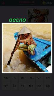 по водоему плывет лодка и человек веслом гребет