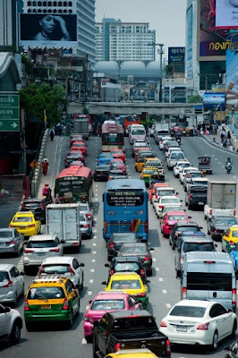 A traffic jam of cars, busses, and vans, in a busy highway