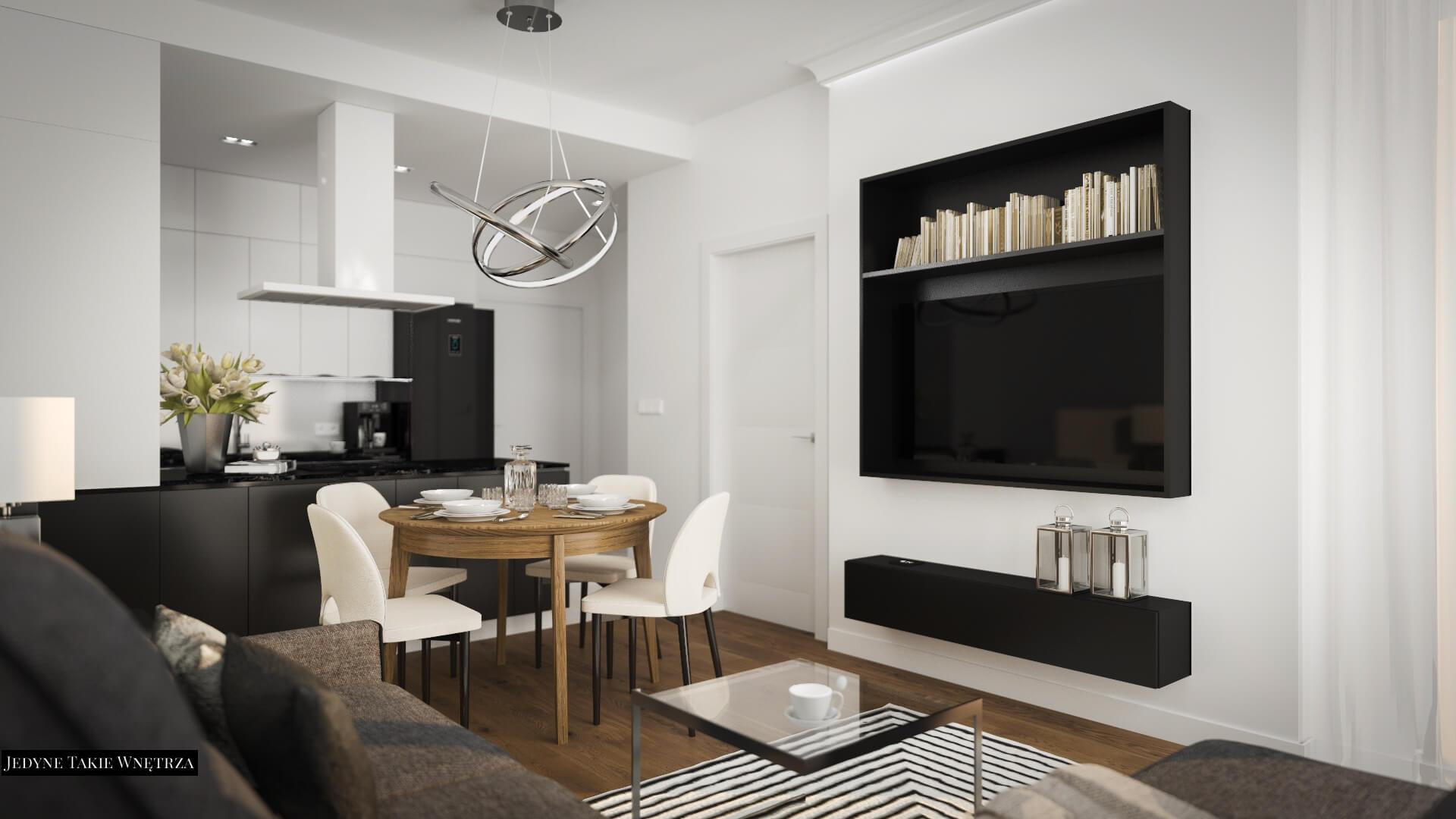 Nowoczesny salon, elegancka czarno-biała kuchnia, obok której znajduje się drewniany stolik z czterema białymi krzesłami.