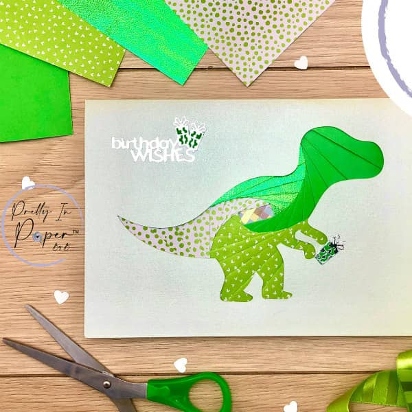 iris folded dinosaur birthday card on table surrounded by paper crafting supplies