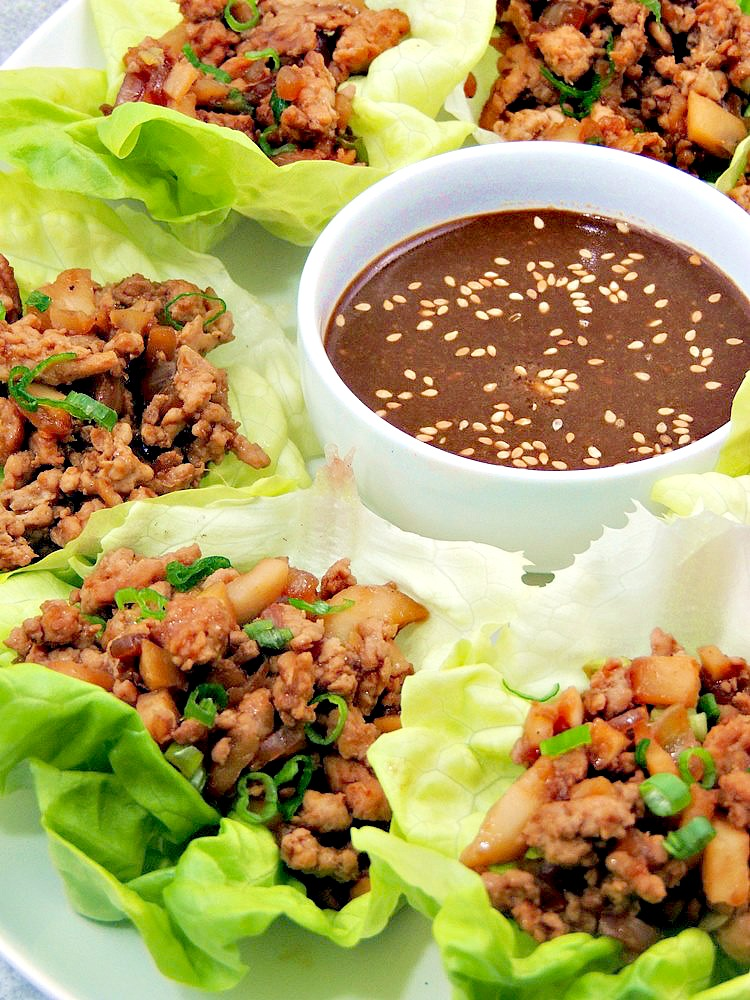 Closeup photo of Copycat PF Chang's Chicken Lettuce Wraps on a white serving tray with a bowl of dipping sauce.
