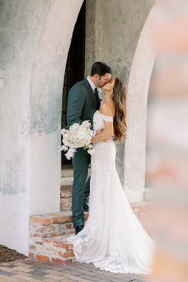 bride and groom kissing with white bouquet