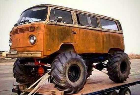Old orange VW bus with huge suspension lift and offroad tires