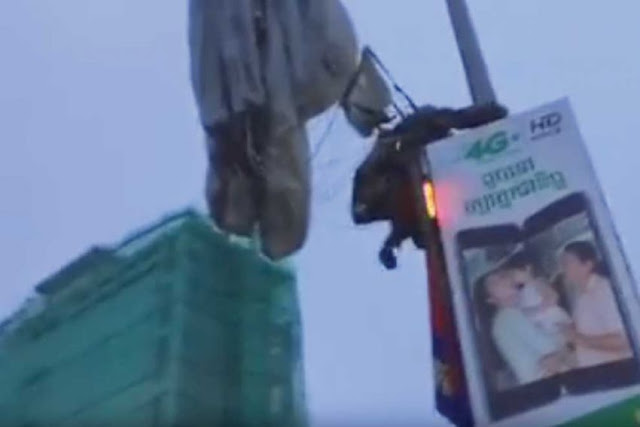 A soldier with the 911 paratrooper brigade clutches a lamppost in Phnom Penh after missing his landing area. YouTube