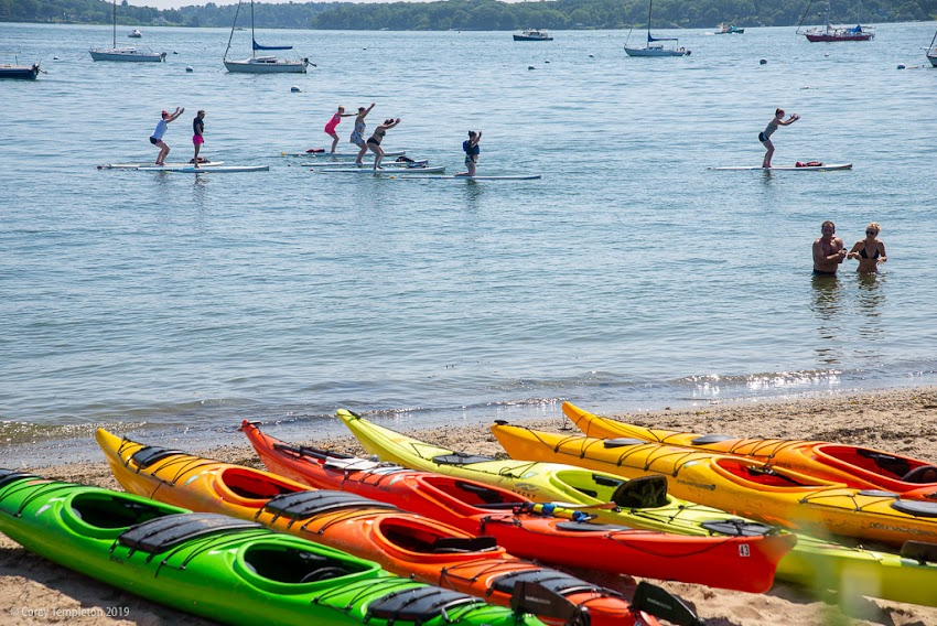 Portland, Maine USA July 2019 photo by Corey Templeton. A paddleboard yoga class in session at the East End Beach.