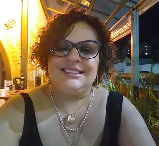 Mulher morena, cabelos curtos cacheados, usa óculos e blusa preta e alças