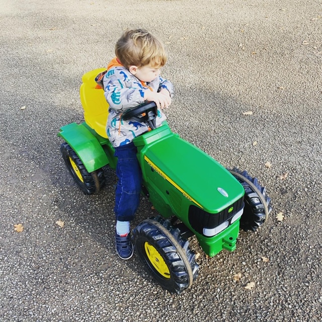 Little boy on a green pedal tractor
