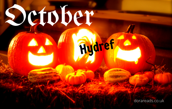 'October - Hydref' with carved, lit, pumpkins in the background