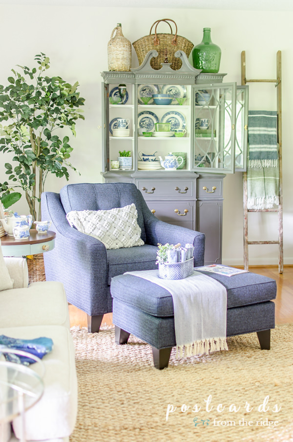 living room with blue and white furniture and old ladder repurposed as a blanket rack