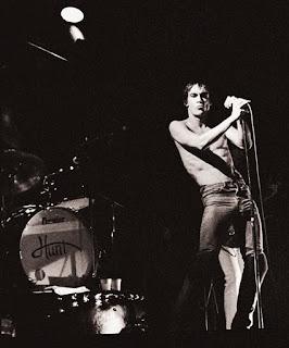 Imgen en blanco y negro de Iggy Pop en una actuación de 1977. Lleva el torso desnudo y agarra el micrófono con ambas manos