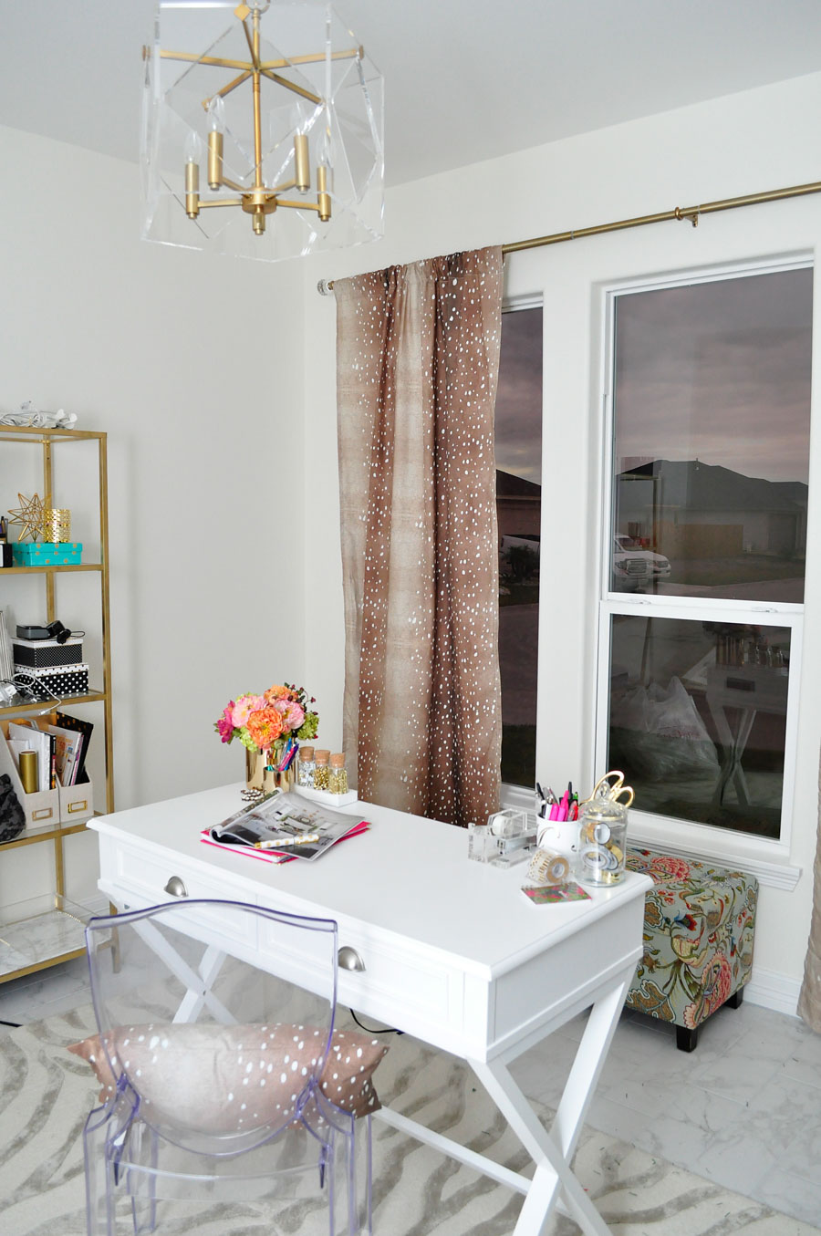 Home office with gold bookshelves, a white desk and fawn print curtains