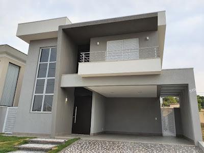 Nesta fachada, a empena que salienta o acesso social da casa se converte em beiral sobre a sacada do pavimento superior.
