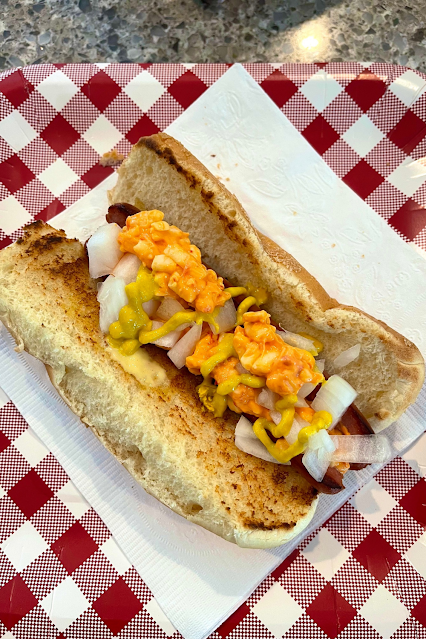 A butterflied hot dog covered in melty pimento cheese on a toasted bun.