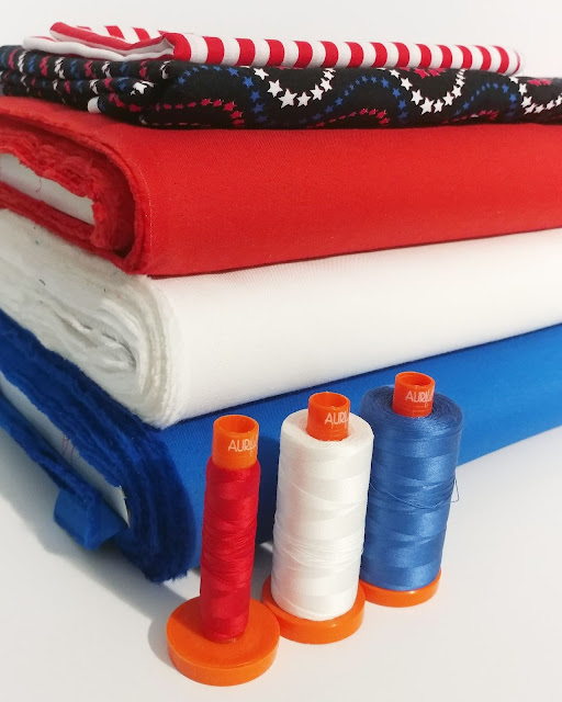 Red white and blue fabrics and thread for a vote love quilt