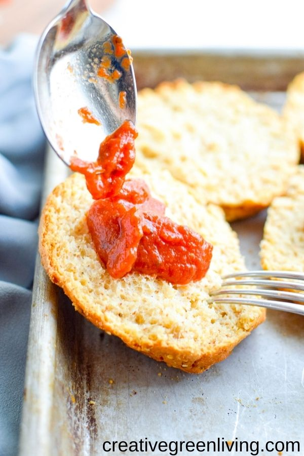 Spooning tomato based pizza sauce onto engish muffins - Use Canyon Bakehouse English muffins to make an easy crust for gluten free mini pizzas! They make a perfect pizza base for this easy kid friendly lunch recipe. Personalize them any way - even make them dairy free or vegetarian. Let kids choose their own healthy toppings for DIY personal pizza activity.