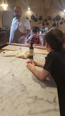 A chef teaches kids to roll out pasta on a marble slab