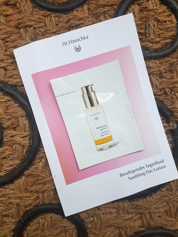 Dr. Hauschka Soothing Day Lotion sample sachet on a brown and black textured mat