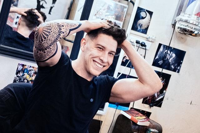 Hombre con ambos brazos sobre la cabeza mostrando un tatuaje en su codo derecho que abarca parte del brazo y antebrazo