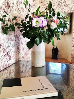 bouquet et livre posés sur un meuble dans la chambre du château de riell