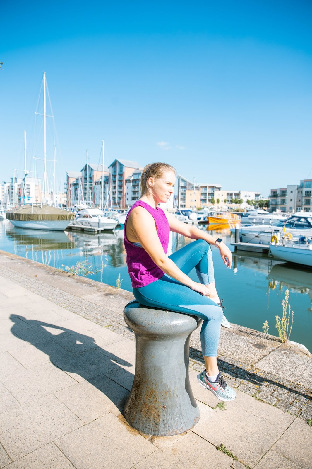 Fitness | The London Marathon Journey - Part 1 - Rachel Emily sitting in Portishead harbour in blue and purple running gear