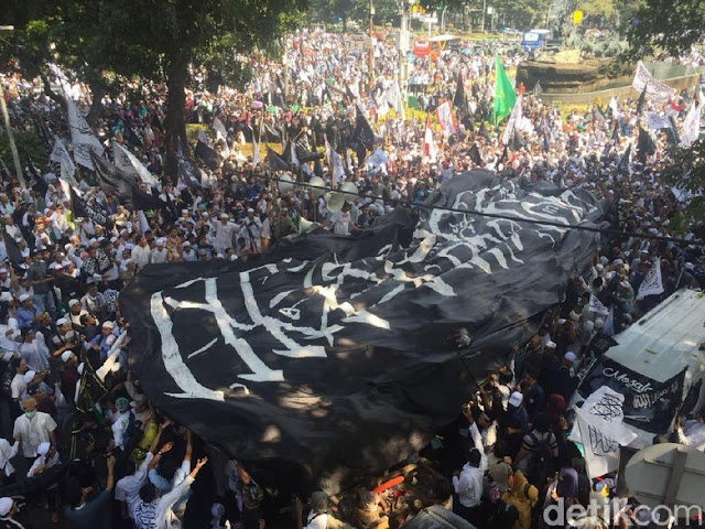 Massa Bentangkan Bendera Berkalimat Tauhid Raksasa di Medan Merdeka