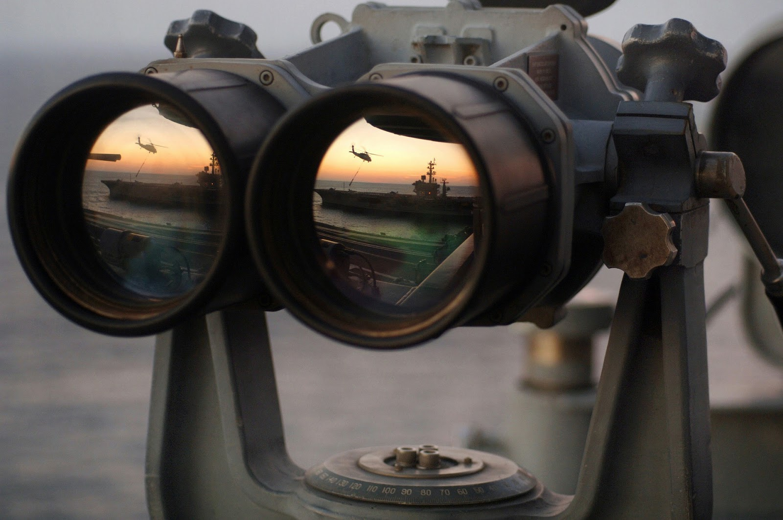mounted miltary binoculars with navy ship reflected in lenses to illustrate war movie operation oblivion