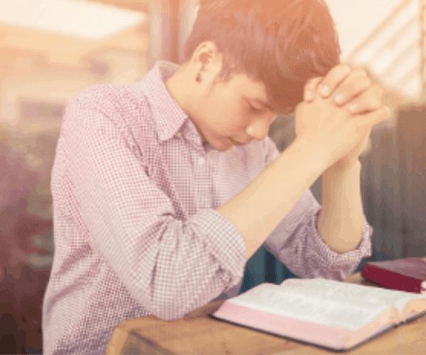 A imagem mostra um jovem cristão com mãos cruzadas orando apoiado em uma mesa com uma bíblia aberta a sua frente. A fotografia possui um tom amarelado.