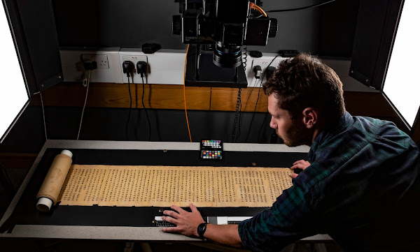 Photograph of man with back to camera in black shirt looking over long yellowed scroll in front of machinery with many cables.