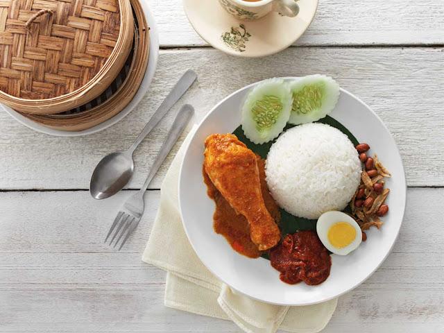 """Nasi lemak được xem như """"quốc thực"""" ở Malaysia và có thể dùng vào mọi buổi trong ngày. Trong các bữa sáng, người dân nước này rất thích ăn món cơm cốt dừa thơm ngậy để nạp năng lượng cho một ngày làm việc mới. Nasi lemak có công thức đơn giản khi được làm từ gạo nấu nước dừa ăn kèm hải sản hoặc thịt bò, thịt gà rồi rắc thêm đậu phộng rang, cá khô."""
