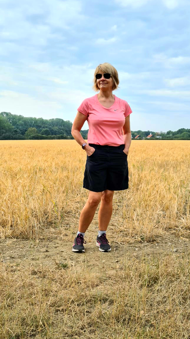 Woman  in shorts and trainers in corn field