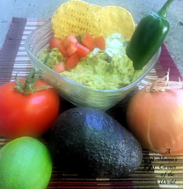 A bowl of guacamole with some of the fresh, whole ingredients surrounding it