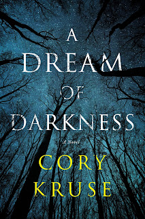 Cover of the Book A Dream of Darkness by Cory Kruse, with title in white and author name in yellow, both in an all- caps serif font, and black tree branches reaching towards a starry blue sky in the background