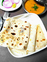 Serving folded rumali roti with curry, onion slice in background