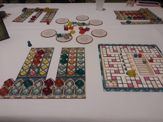 A game of Azul: Stained Glass of Sintra in progress. Several player boards with translucent coloured tiles arranged on them. Seven round discs, one with four of the coloured tiles on it, sit in a ring in the centre of the table, with a number of the coloured tiles in the centre of the circle. There is a score tracker nearby, with coloured scoring markers on it.