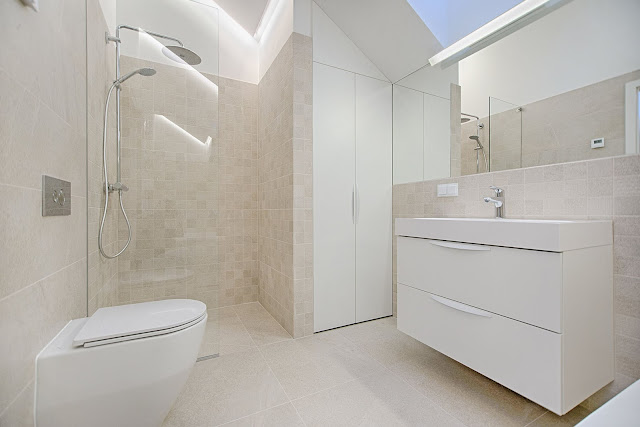 cream bathroom with white toilet, sink and cabinet, chrome shower