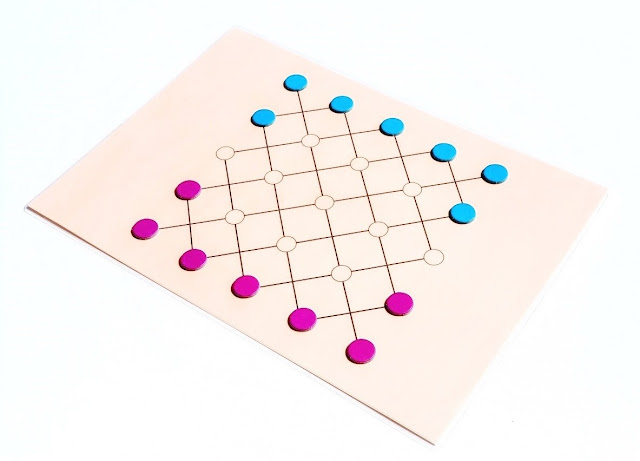 zdjęcie przedstawia plansze do gry w kolorze kremowym a na niej po siedem pionków w dwóch kolorach różowym i niebieskim