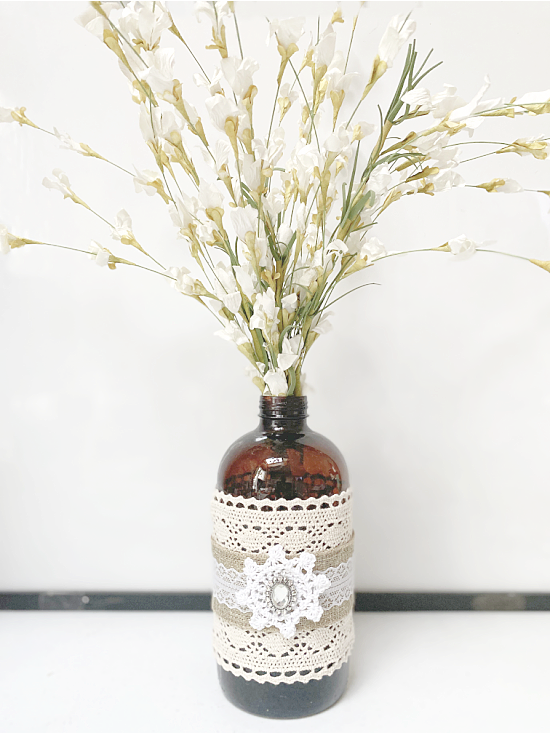 Amber bottle with lace filled with flowers